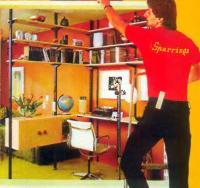 Комнату угловой стеллаж может поделить на гостиную и кабинет